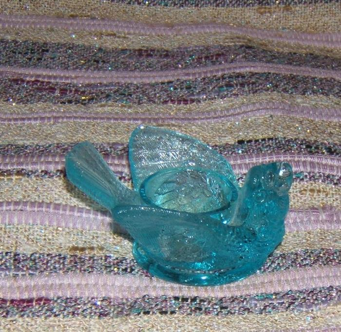 blue glass bird with berry in its beak