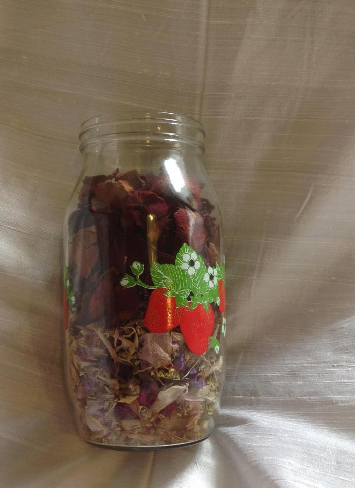 a jar of rose petals and other flowers from a saved bouquet